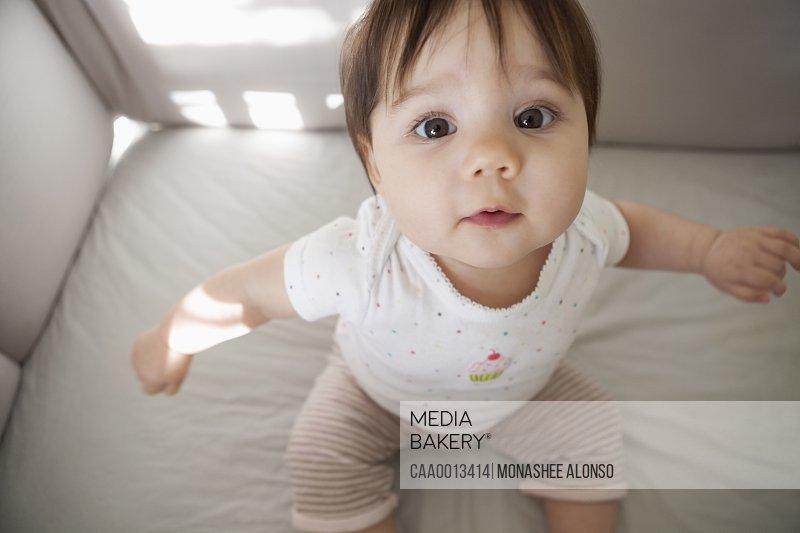 Baby girl sitting up in crib