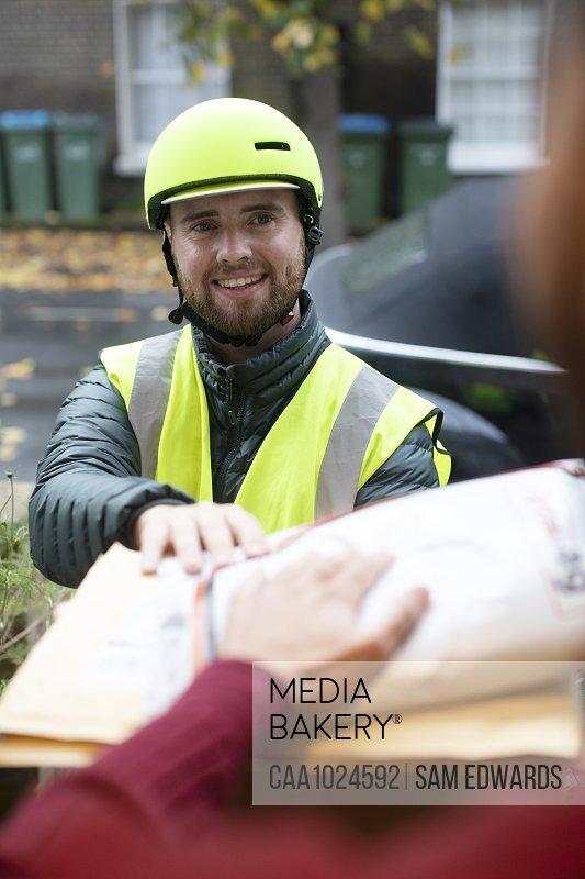 Friendly male bike messenger in helmet making delivery at door