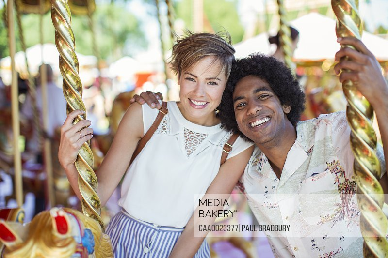 Young multiracial couple smiling on carousel in amusement park