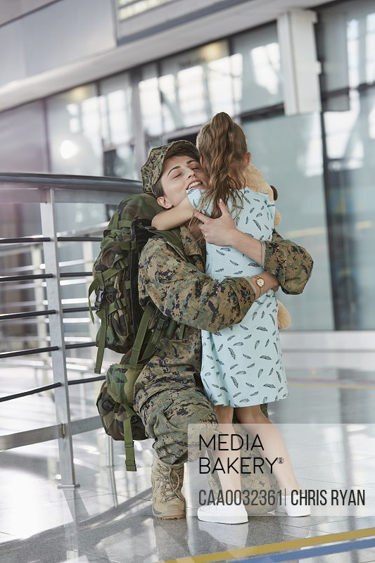 Daughter greeting hugging soldier mother at airport