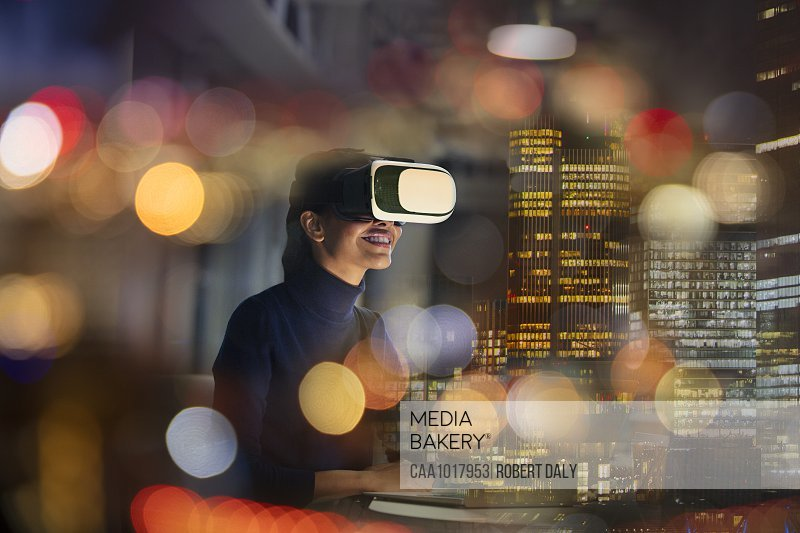 Businesswoman with virtual reality glasses in highrise office at night