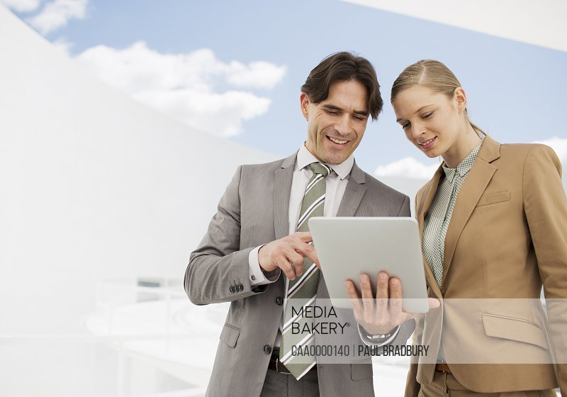 Businessman and businesswoman using digital tablet