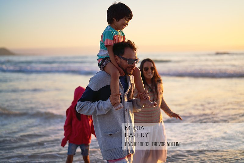 Happy family wading in ocean at sunset
