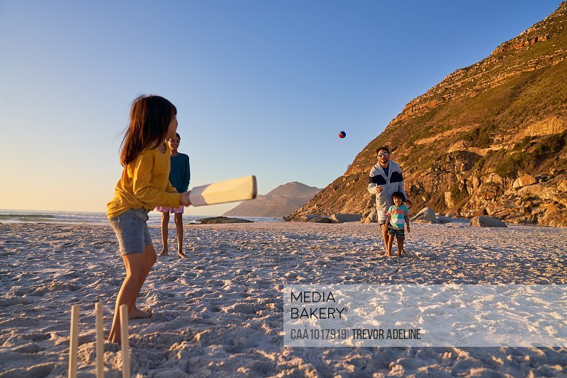 Family playing cricket on sunny beach
