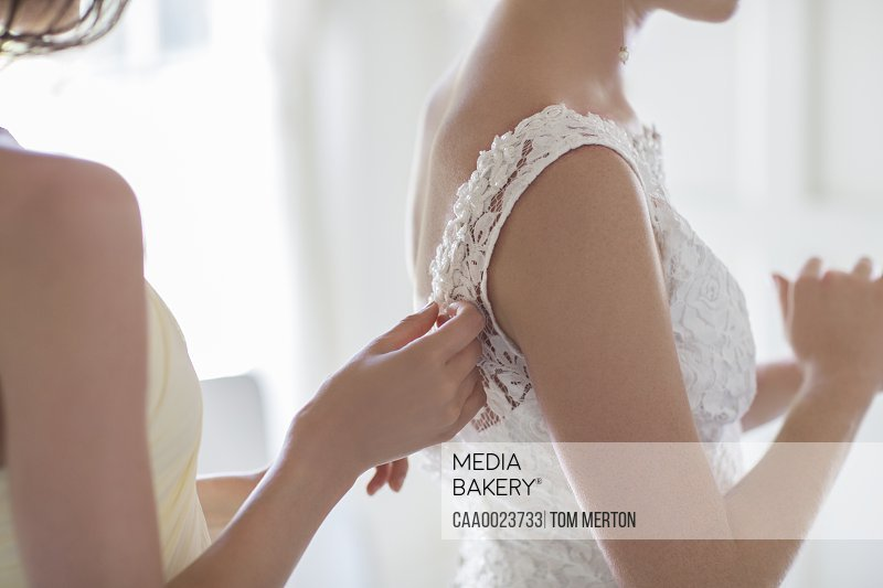 Bridesmaid helping bride with dressing in domestic room
