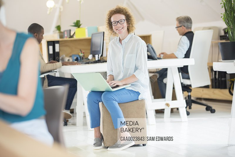 Portrait of woman holding laptop at office