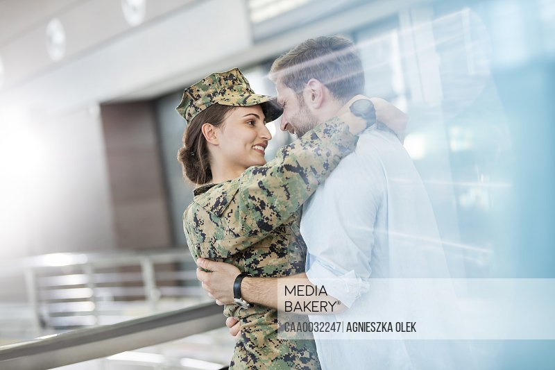 Husband greeting hugging soldier wife at airport