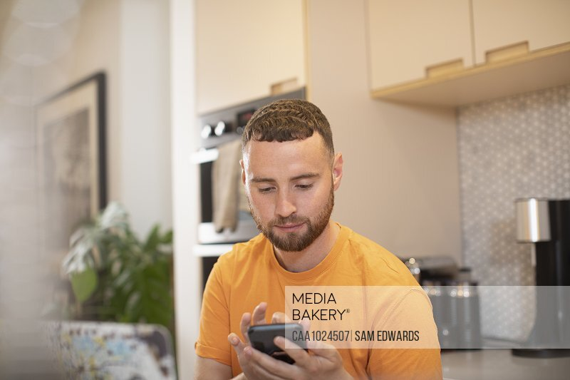 Young man using smart phone in kitchen