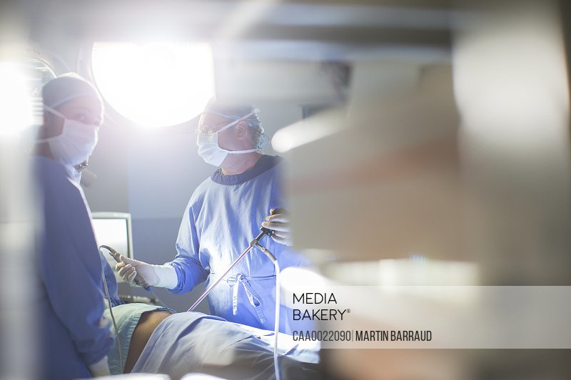 Doctors performing laparoscopic surgery in operating theater
