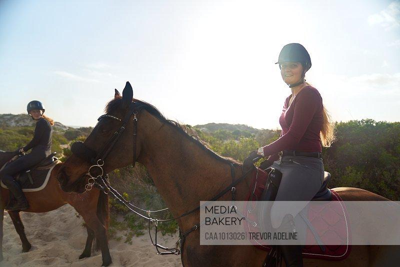 Portrait happy young woman horseback riding on sunny beach
