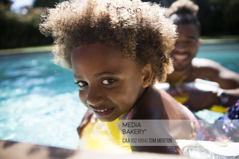 Portrait cute girl with curly hair in sunny summer swimming pool