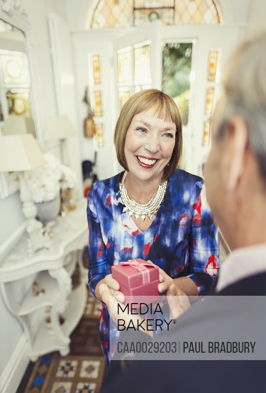 Smiling mature woman receiving gift from husband