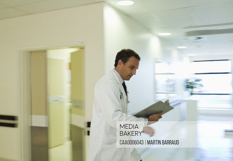 Doctor reading medical chart in hospital hallway
