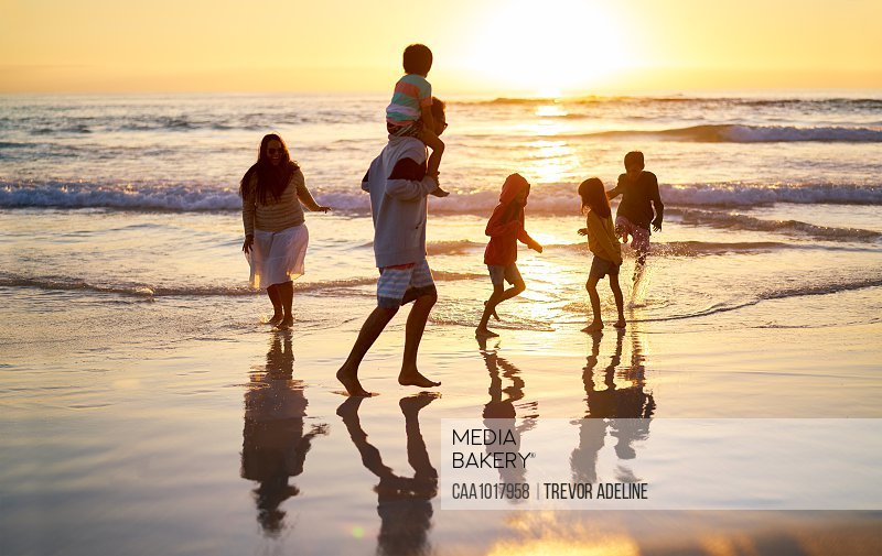 Family wading in surf on idyllic ocean beach at sunset