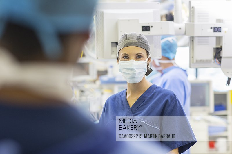 Female doctor wearing surgical cap and mask looking at camera