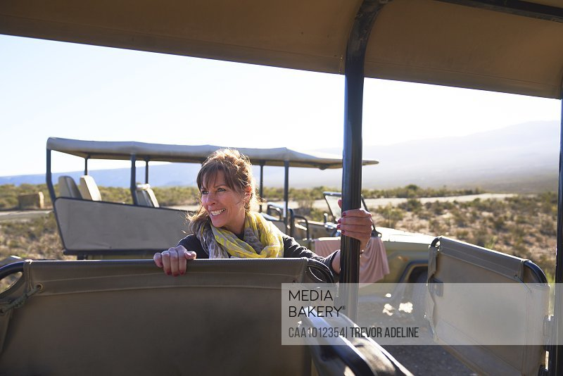 Happy mature woman getting into safari off-road vehicle