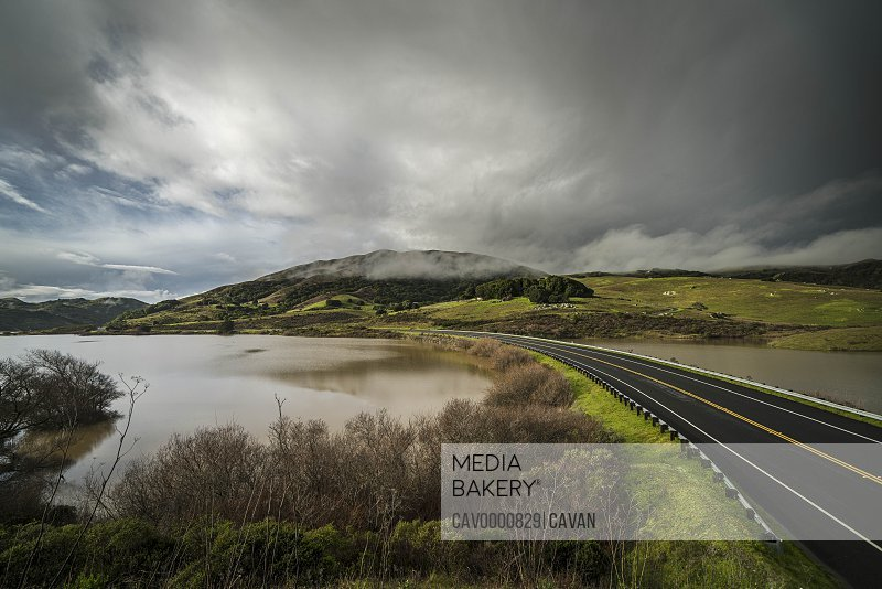 Empty road between two reservoirs with green hills and  storm clouds
