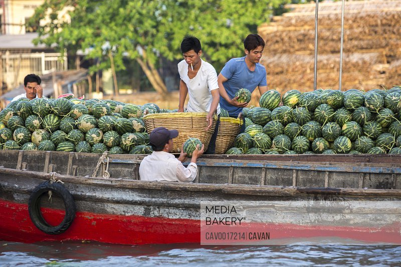 Men sell watermelons from a boat at the floating market in the Mekong. <br><br><span style='color: red'>Editorial Use Only.</span><br><br>