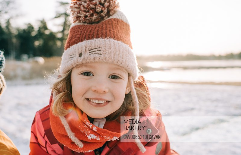 close up portrait of a young girl sitting in the snow at sunset