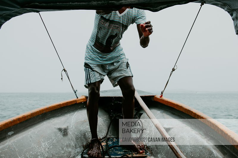 Local Colombian fisherman grips the roof of his tinny on rough seas