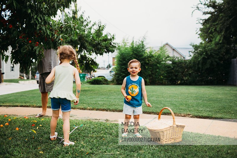 Young girl and boy standing in front yard picking peaches with grandpa