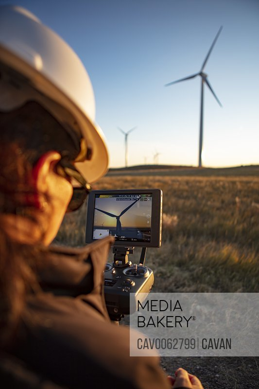 Female drone pilot flies in a wind farm at sunrise