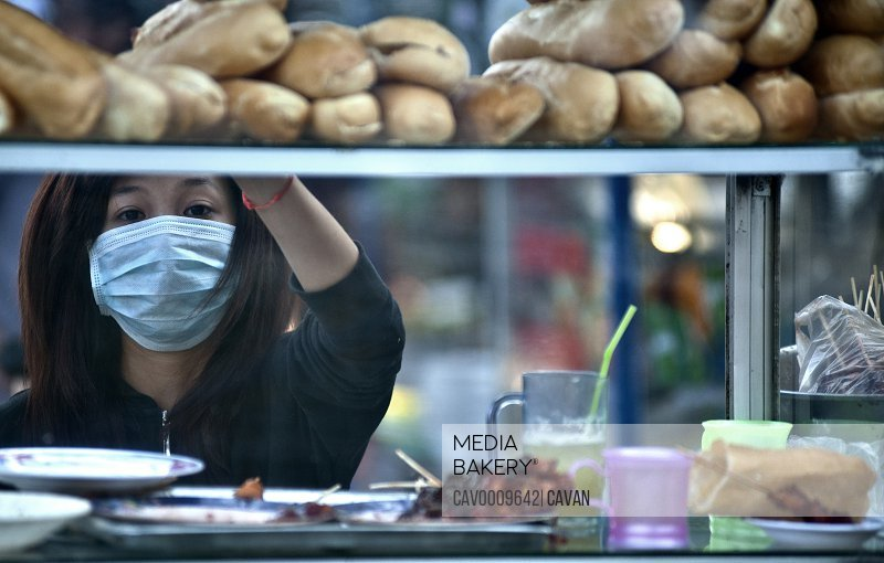 Woman works in the streets food business wearing anti-pollution mask <br><br><span style='color: red'>Editorial Use Only.</span><br><br>