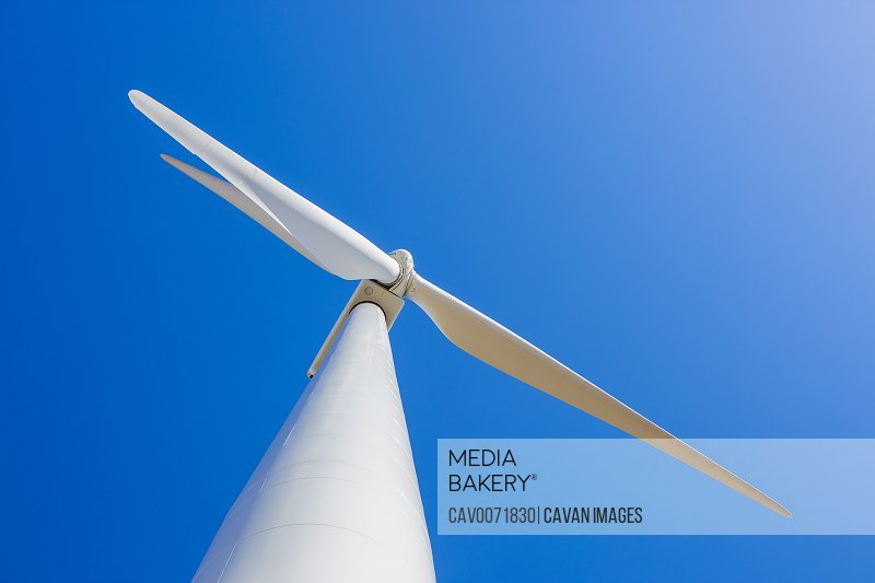 Wind Turbine against blue sky from low angle
