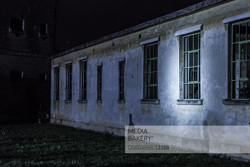 Searchlight glow on old prison building