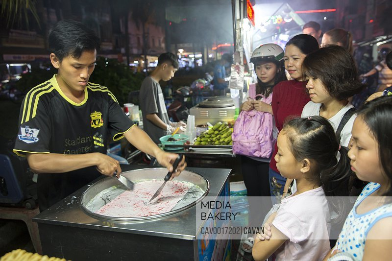 A crowd watches a man makes rolled ice-cream in Vietnam. <br><br><span style='color: red'>Editorial Use Only.</span><br><br>