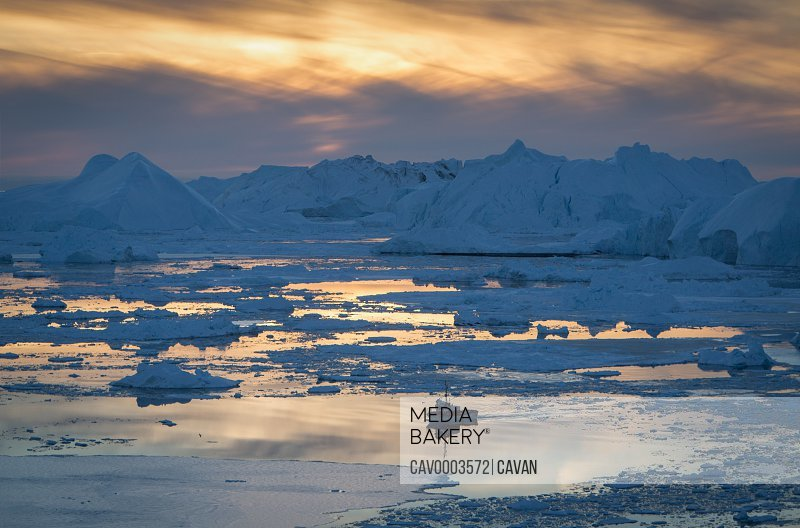 Ship sailing on ocean at sunset with icebergs in background, Greenland