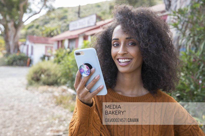 Portrait of black woman holding smartphone smiling looking at camera