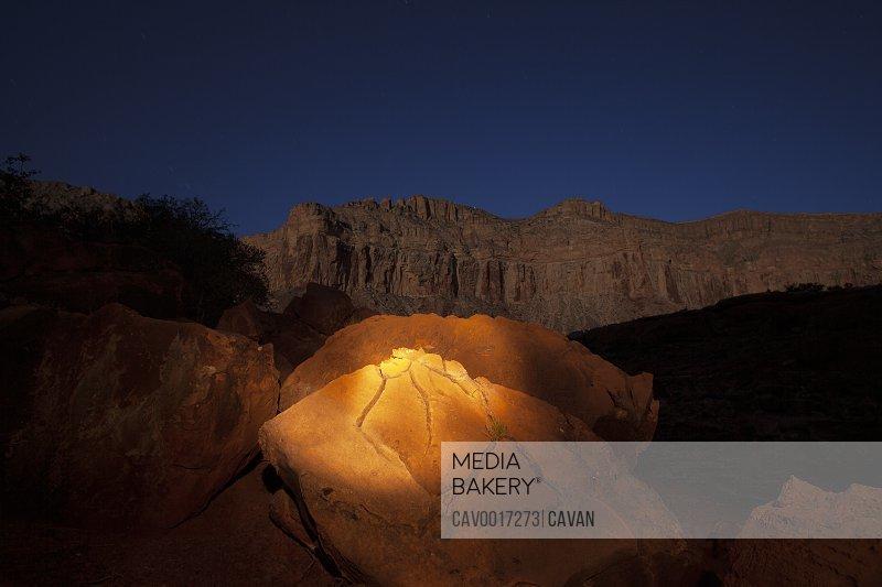 The orange glow of a flashlight illuminates a cracked rock at night
