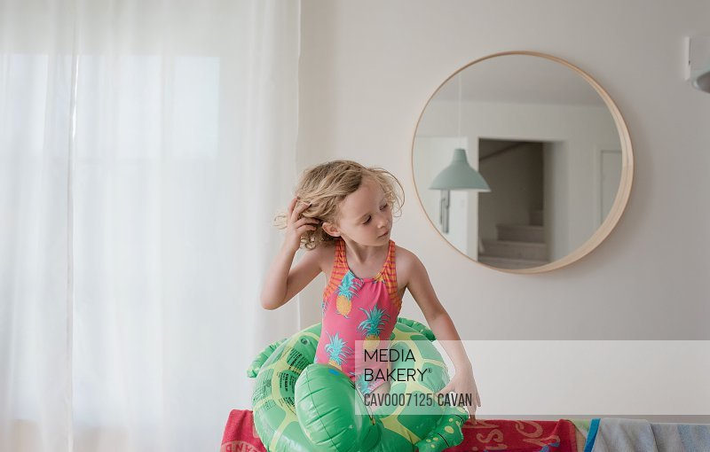 young girl with inflatable ring and swimming costume stood at home