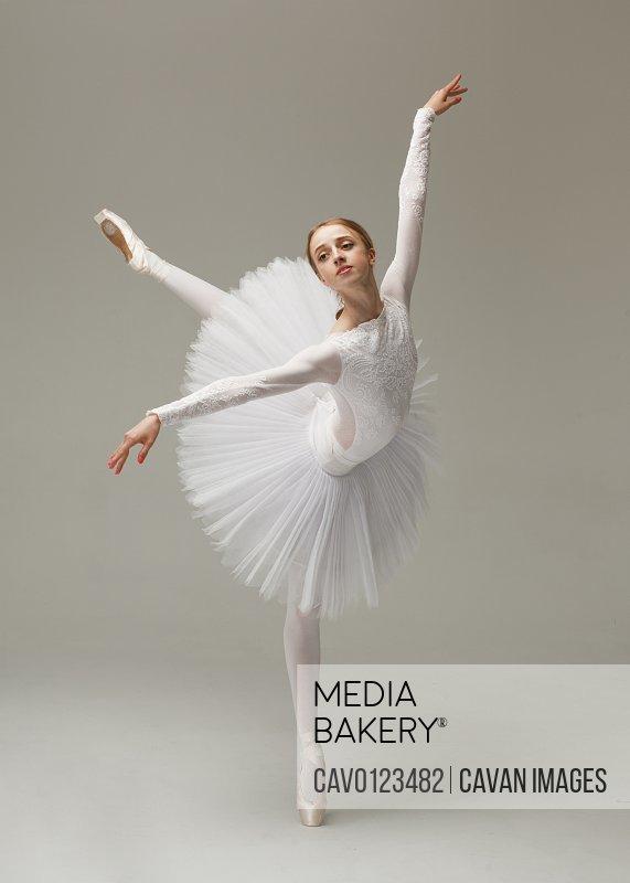 beautiful female ballet dancer in white ballet dress dancing tiptoe