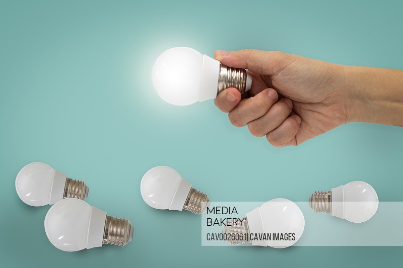 Hand holding illuminated light bulb, idea, inspiration concept