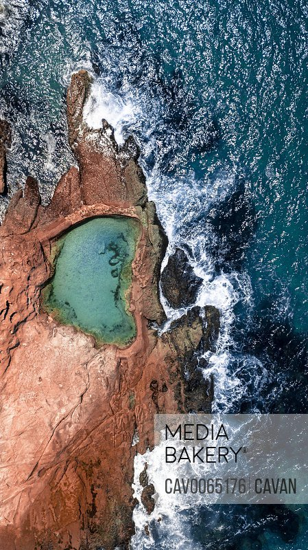 Aerial shot of filled Rockpool near coastline with waves crashing in