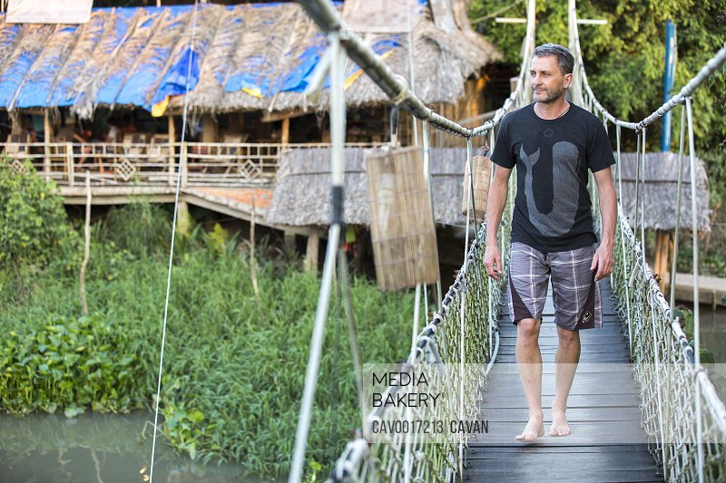 A man walk on a suspension bridge in rustic setting. <br><br><span style='color: red'>Editorial Use Only.</span><br><br>