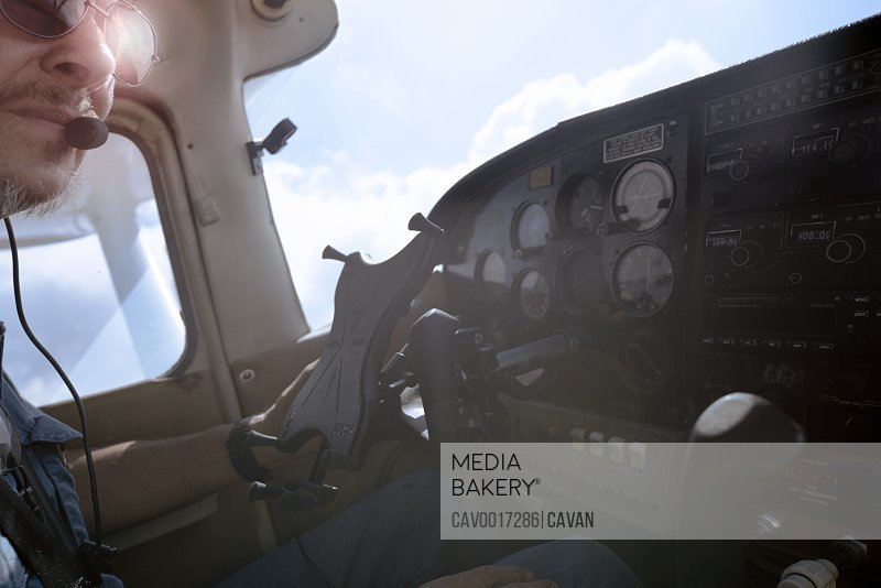 View inside the cockpit of a small airplane with pilot looking off <br><br><span style='color: red'>Editorial Use Only.</span><br><br>