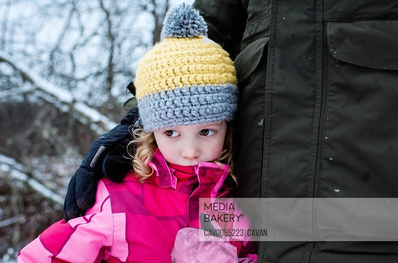 young girl looking sad cuddling her dad whilst playing outside in snow