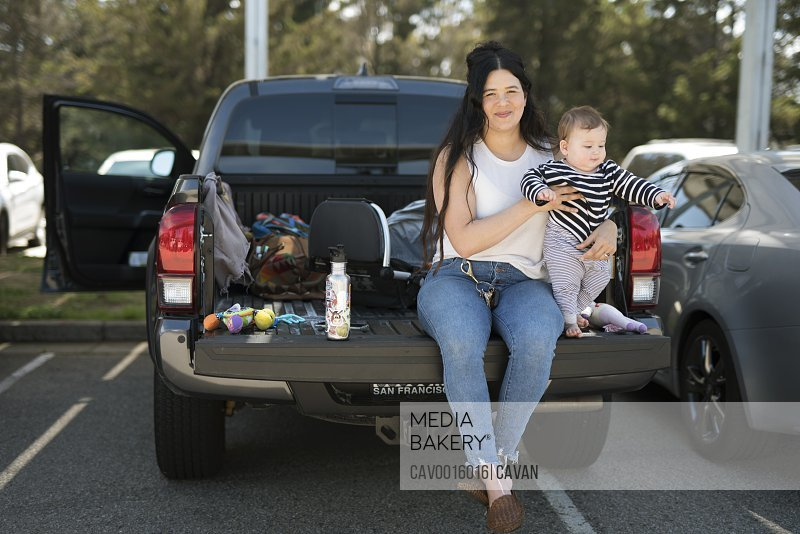 A young woman and her baby sit on tailgate of a truck at a rest stop.