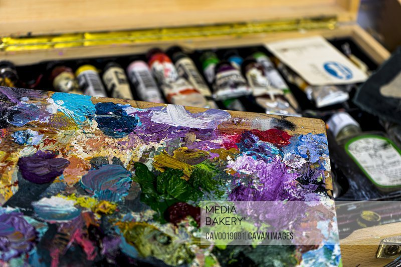 Painter's palette with traces of oil paintings with their respective set of paintings.