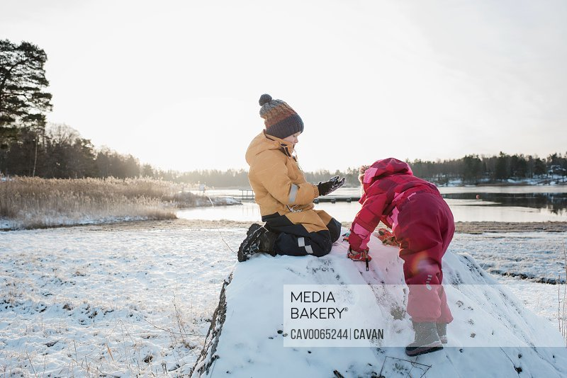 siblings playing together by the Baltic Sea in the snow at winter
