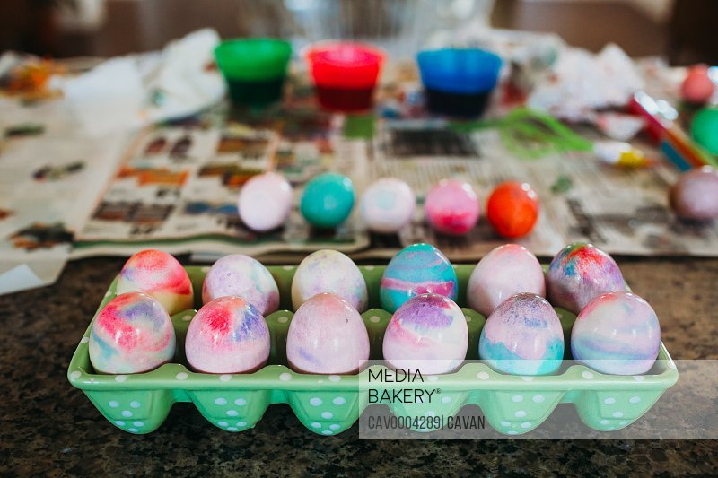 Dozen colorful dyed easter eggs sitting on kitchen counter