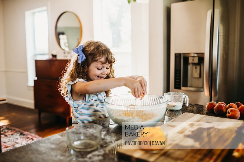Young girl smiling and cracking raw egg into fresh peach muffin batter