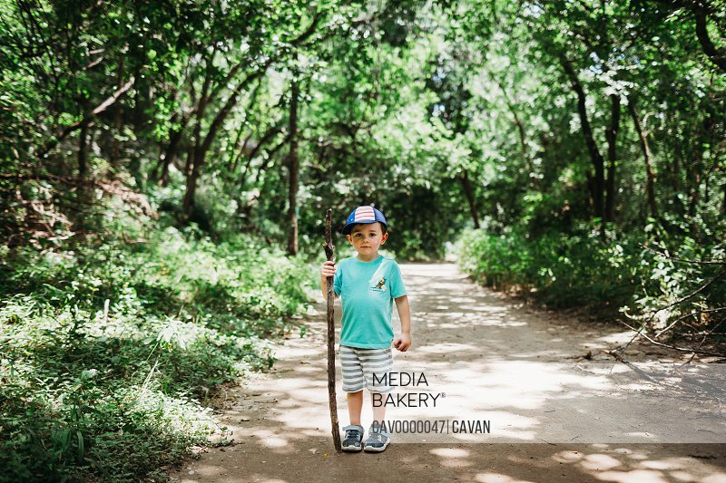 Young boy hiking and using walking stick with hat on