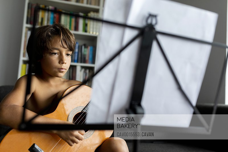young boy playing guitar in front music stand