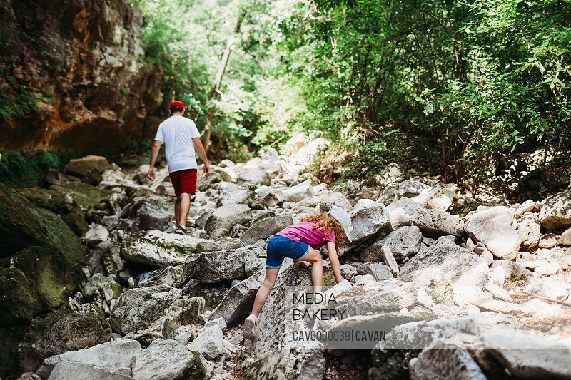 Young girl climbing rocks while hiking with dad