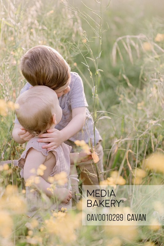 Big Brother Hugs Baby Sister in a Field