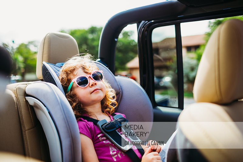 Young girl wearing sunglasses and riding in car with top off